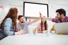 Male colleagues giving high-five in meeting at creative office Stock Photography