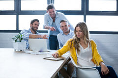 Male colleagues laughing on businesswoman Royalty Free Stock Photos