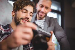 Male colleagues smiling while looking in camera. Low angle view of male colleagues smiling while looking in camera at creative office royalty free stock photo