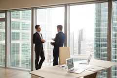 Male colleagues taking coffee-break in office. Two businessmen having coffee while standing near large window. Coworkers discussing work, talking about Stock Photos