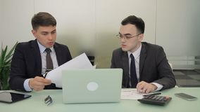 Male colleagues talking while sitting at desk with laptop in company. Young men communicate actively, discuss working issues, examining documents and looking stock video footage