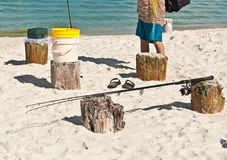Male collecting fishing gear resting on wood pilings on a sandy, tropical beach on the Gulf of Mexico Stock Image