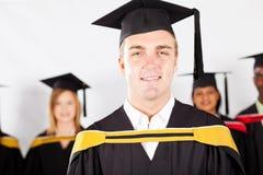 Male college graduate. Happy male college graduate with classmates at graduation Stock Photo