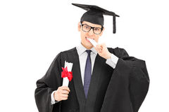 Male college graduate biting his worthless diploma Stock Image
