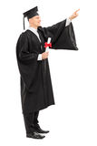 Male college graduate with a diploma pointing up Royalty Free Stock Photos