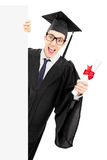 Male college graduate holding diploma and peeking behind blank p Stock Photos
