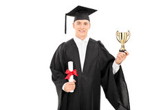 Male college graduate holding a golden trophy Royalty Free Stock Image