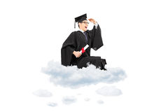 Male college graduate seated on cloud and looking in distance Stock Photo