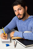 Male college student with books and notepad. Young student taking notes and studying. Holding yellow pencil and black background Stock Photos