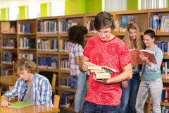 Male college student holding books in library. Portrait of male college student holding books in the library Stock Photography