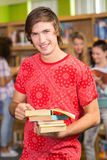 Male college student holding books in library. Portrait of male college student holding books in the library Stock Images