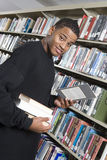 Male College Student At Library. Portrait of an African American men reading book while standing by a bookshelf Royalty Free Stock Photo