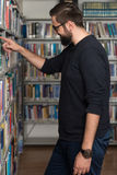 Male College Student In A Library. Portrait Of An Caucasian College Student Man In Library - Shallow Depth Of Field Royalty Free Stock Photos