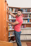 Male College Student In A Library. Portrait Of A College Student Man In Library - Shallow Depth Of Field Royalty Free Stock Image