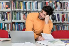 Tired Student Working With Laptop in the Library. Male College Student Looks Tired While Studying With a Laptop and Textbooks in the Library Stock Photos