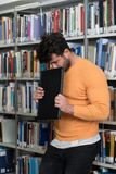 Tired Student Working With Laptop in the Library. Male College Student Looks Tired While Studying With a Laptop and Textbooks in the Library Royalty Free Stock Images