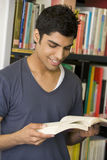 Male college student reading in a library royalty free stock photo