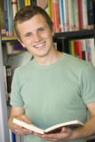 Male college student reading in a library Stock Photo