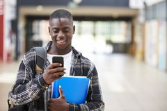 Male College Student Reading Text Message On Mobile Phone Royalty Free Stock Photos