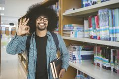 Male student showing OK sign in the library. Male college student showing OK sign while smiling at the camera and standing in the library Royalty Free Stock Image