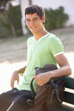 Male College Student Sitting On Bench With Backpack Stock Images