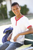 Male College Student Sitting On Bench With Backpack Royalty Free Stock Images