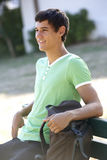 Male College Student Sitting On Bench With Backpack Stock Photo