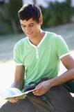 Male College Student Sitting On Bench Reading Textbook Stock Images