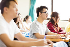 Male college student sitting  with classmates. Smiling male college student sitting  with classmates Royalty Free Stock Photo
