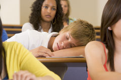 Male college student sleeping through a lecutre. Male college student sleeping through a university lecture Royalty Free Stock Photo