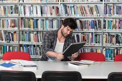 Male College Student Stressed About His Homework. Male College Student Looks Tired While Studying With a Laptop and Textbooks in the Library Royalty Free Stock Photos