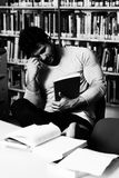 Male College Student Stressed About His Homework. Stressed Young Male Student Reading Textbook While Sitting in Library Royalty Free Stock Images