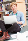Male College Student Studying In Library With Laptop Royalty Free Stock Photo