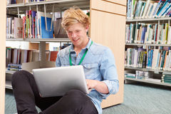 Male College Student Studying In Library With Laptop royalty free stock image
