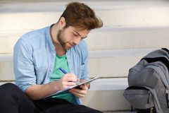 Male college student studying outdoors. Close up portrait of a male college student studying outdoors Stock Images