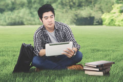 Male college student with tablet in the meadow. Photo of an Asian male college student using a digital tablet while sitting with a bag and books in the meadow Stock Images