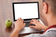 Male college student using laptop. Rear view of young male college student using laptop by green apple on table Royalty Free Stock Images