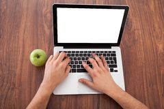 Male college student using laptop. Rear view of young male college student using laptop by green apple on table Stock Images