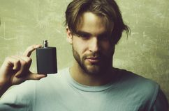 Male cologne. guy with black perfume bottle. Male cologne. guy or caucasian macho hold black perfume or cologne bottle on handsome face with blond hair in white royalty free stock photo