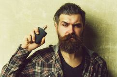 Male cologne. man posing with black perfume bottle. Male cologne. man or brutal caucasian hipster with grey hair, long beard and moustache posing with black royalty free stock image