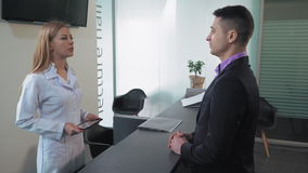 Male come to visit doctor. Adult man in dental clinic or in hospital standing in lobby talking with receptionist . Blonde woman greeting male using computer stock footage