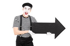 Male comedian holding a big black arrow Royalty Free Stock Image