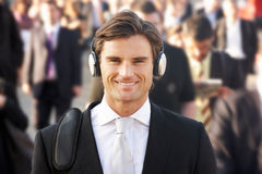 Male commuter in crowd. Wearing headphones stock images