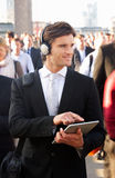 Male commuter in crowd. With tablet and headphones royalty free stock photo
