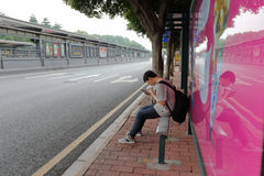 Male commuter sit at bus station Stock Image