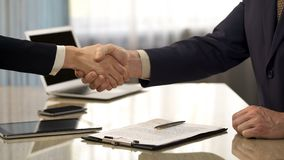 Male concluding business deal, shaking hands with partner, company partnership royalty free stock image