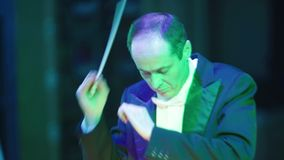 The male conductor conducts the orchestra.