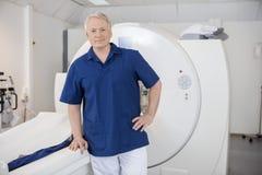 Male Confident Radiologist Leaning On MRI Machine Stock Photos