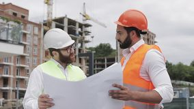 Male construction engineer discussion with architect at construction site or building site of highrise building. They. Holding construction drawings in their stock video footage