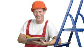 Male construction engineer using digital tablet. Smiling attractive constructor with protective equipment using pc tablet isolated on white background stock footage